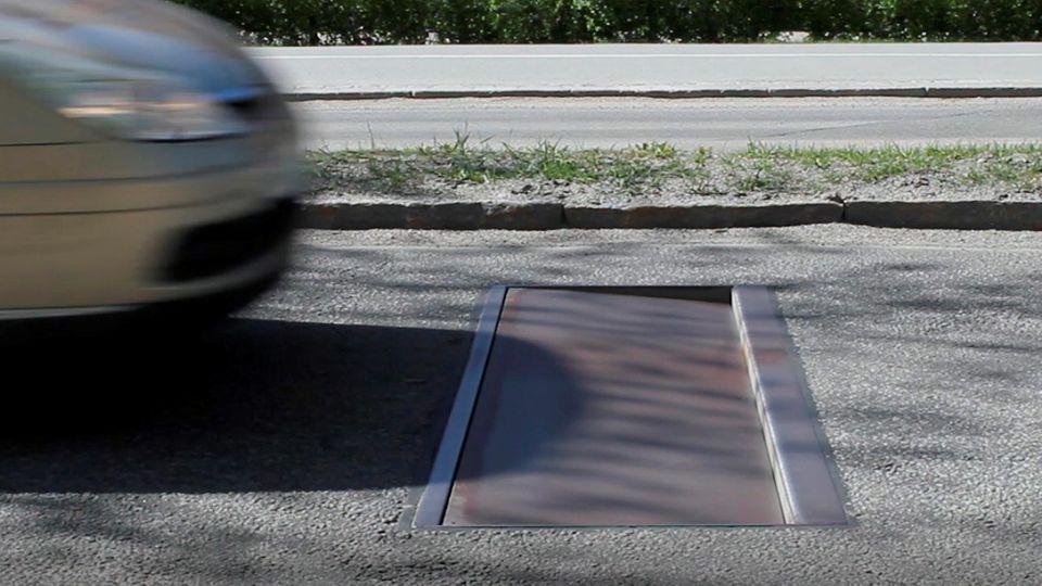 Ein Auto rast auf eine in der Straße eingelassene Stahlplatte zu