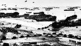 Provisorischer Hafen  Hunderte Schiffe liegen vor der Küste der Normandie. An den breiten Sandstränden entladen landungsboote ihre Fracht. Lastwagen formieren sich zu Marschkolonnen. Über der Szene schweben Fesselballons, die mit ihren Stahltrossen deutschen Fliegern den Weg versperren und so Angriffe verhindern sollen