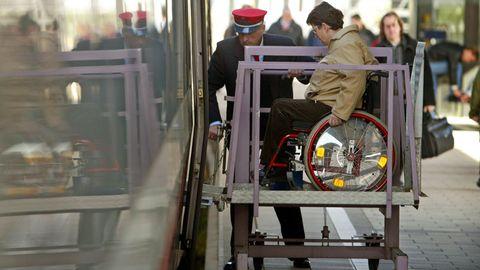Ein Mitarbeiter der Deutschen Bahn hilft einer Frau, in den Zug zu gelangen