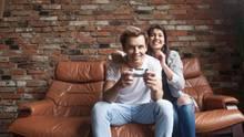 Ein Pärchen sitzt auf einem Ledersofa. Beide lächeln. Er spielt an einer Spielkonsole auf dem Fernseher. Sie schaut zu.