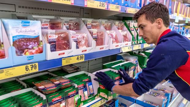Ein Verkäufer räumt Regale in einem Lidl-Supermarkt ein