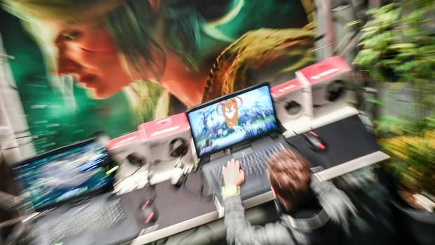 Ein Junge spielt ein Computerspiel, er sitzt vor einer Wand, auf die der Kopf einer Frau gemalt ist