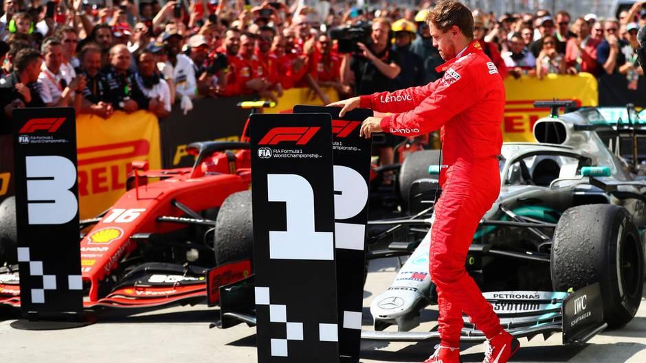 Sebastian Vettel beim Tauschen des Siegeraufstellers vor den Formel-1-Wagen.
