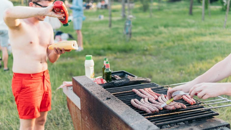Mann mit roter Badehose hält Hotdog