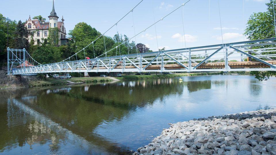 Blick auf die Hängebrücke über der Mulde. Im Hintergrund ist die Gattersburg zu sehen.