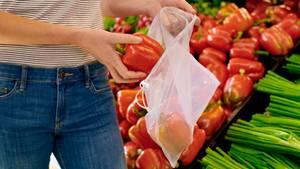 Hände legen eine rote Paprika in einen durchsichtigen Beutel