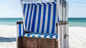 Ein blau gestreifter Strandkorb steht an einem Strand.
