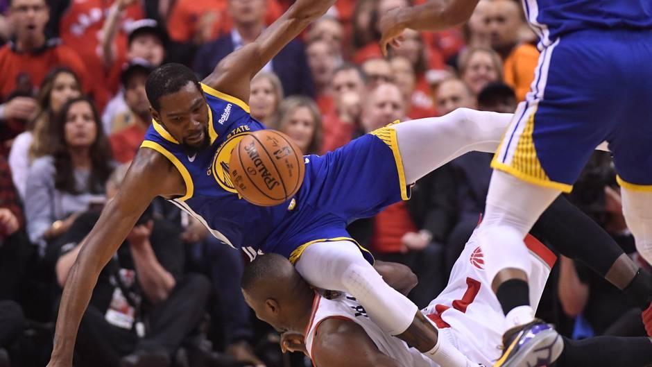 Kevin Durant (l.) von den Golden State Warriorsfällt über den Toronto Raptors-Spieler Serge Ibaka