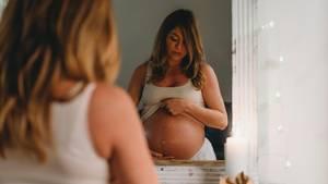 Eine junge, schwangere Frau steht vor dem Spiegel und schaut auf ihren Bauch. Darauf sieht man einen vertikalen Streifen