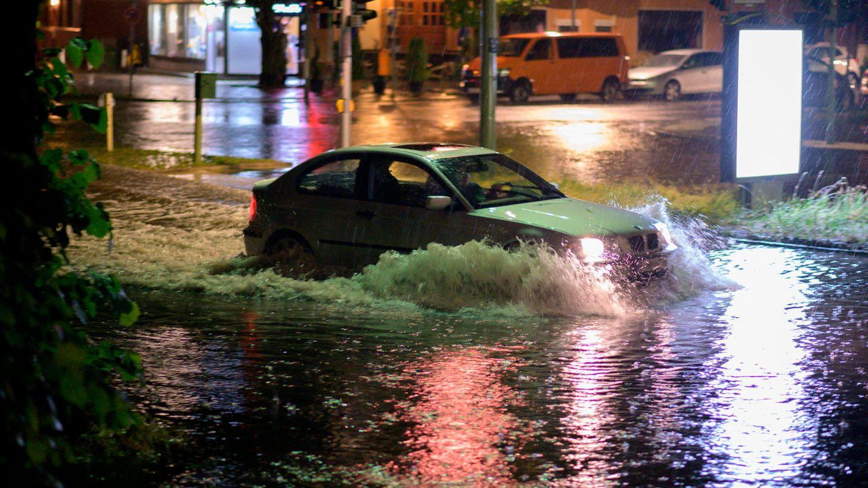 Ein Pkw fährt nach einem Gewitter mit heftigem Regen durch die überflutete Breite Straße in Berlin-Schmargendorf