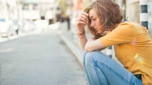 Trauriges Mädchen, das auf dem Boden sitzt.