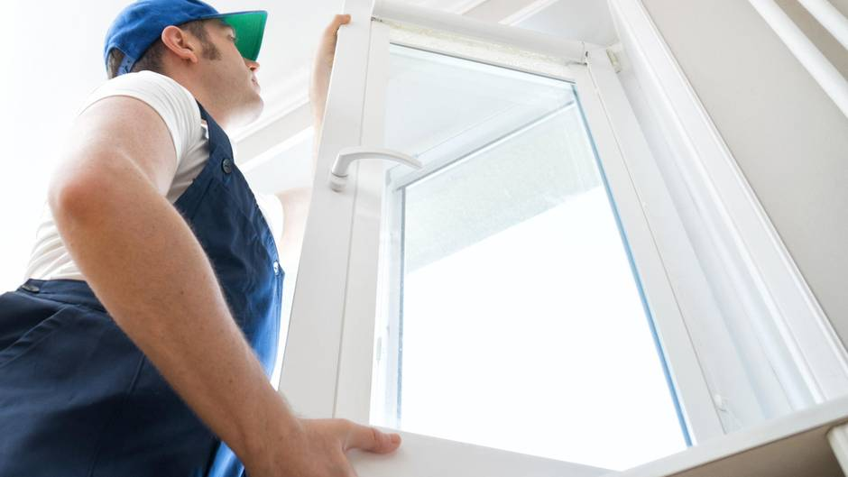 Ein Handwerker setzt ein neues Fenster ein