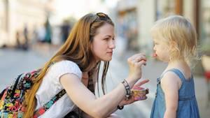 Eine Frau füttert ein Kind mit Eis