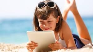 Ein Mädchen liegt am Strand und schaut auf ihr Tablet