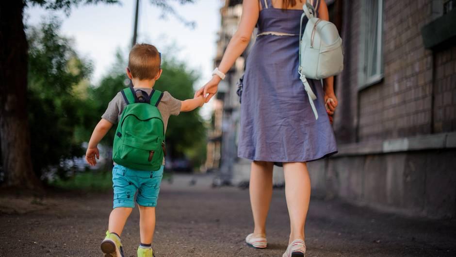 Frau mit Kind an der Hand