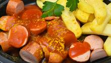 Eine in Stücke geschnittene Wurst liegt in einer Currysauce. Daneben Pommes und ein wenig glatte Petersilie