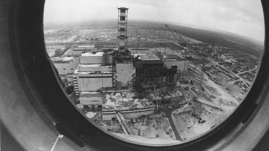 Ein Schwarz-weiß-Foto zeigt den explodierten Reaktor von Tschernobyl durch ein rundes Hubschrauber-Fenster