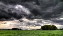 Ein Feld und Gewitterwolken