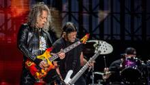 Ein langhaariger Mann mit E-Gitarre und ein Bassist mit schwarzen Zöpfen stehen nebeneinander auf einer Bühne