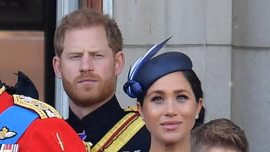Prinz Harry steht hinter seiner Frau, Herzogin Meghan, und schaut streng