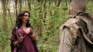 In einem Wald steht eine Frau in tief ausgeschnittenem roten Kleid und ihre übergroßen Brüste schauen hervor