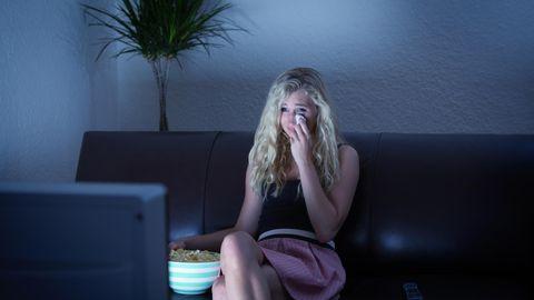 Frau weint vor dem Fernseher