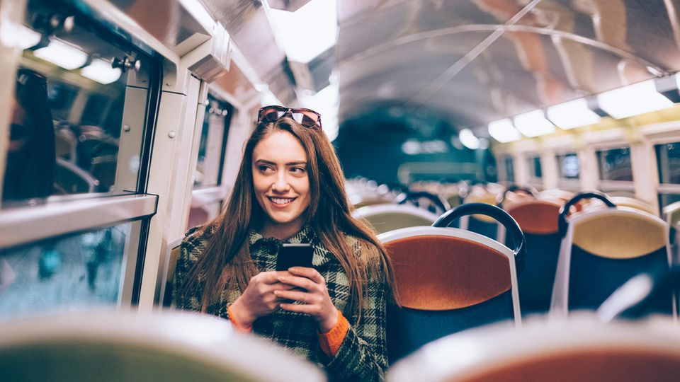 Frau sitzt in Bahn mit Handy in der Hand