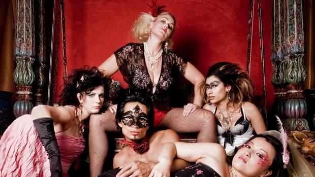 Eine Gruppe von Prostituierten vor einer roten Wand