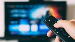 Hand mit Fernbedienung und Fernseher unscharf