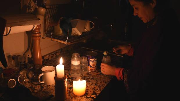 Das Leben bei Stromausfall: Bei Kerzenlicht macht diese Frau in Montevideo eine Milchflasche für ihr Baby fertig