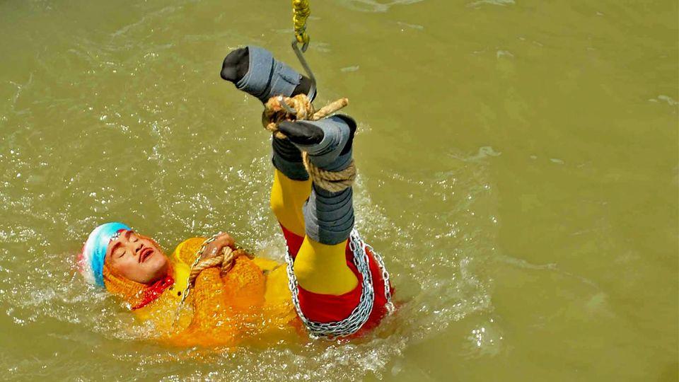 it einem Seil und Ketten gefesselt hat sich ein Zauberkünstler in Indien in den Ganges fallen lassen