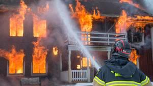 Ein Feuerwehrmann löscht ein brennendes Haus
