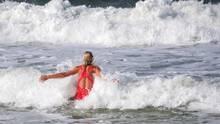 Eine blonde Frau im roten Badeanzug springt in die Wellen der Nordsee vor Sylt