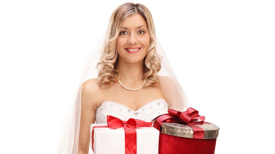Blonde Braut hält drei Hochzeitsgeschenke in ihren Händen und grinst