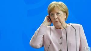 Angela Merkel mit Hand am Ohrhörer - kein Grund zur Sorge nach Zitter-Anfall
