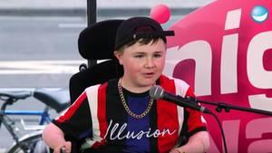 Der 14-jährige Carl Josef sitzt im Rollstuhl auf der Bühne