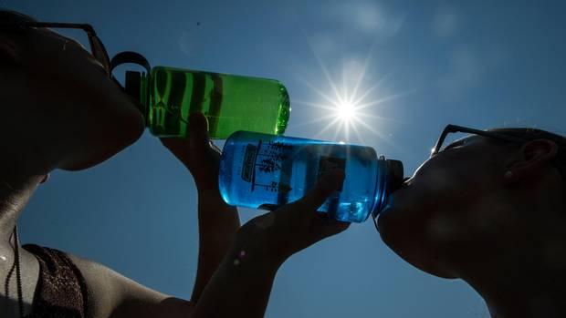 Zwei Frauen trinken bei Sonnenschein Wasser aus einer Flasche
