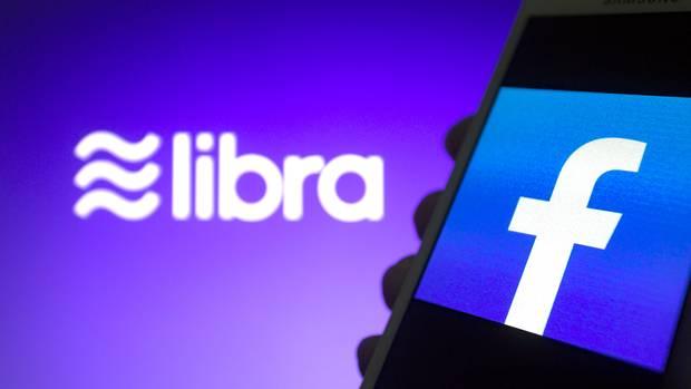 Das Libra-Logo ist vor einem Smartphone mit Facebook-Logo zu sehen