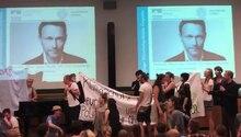 Auf einer Bühne stehen junge Menschen mit Bannern, im Hintergrund sind zwei Porträts von Christian Lindner projeziert