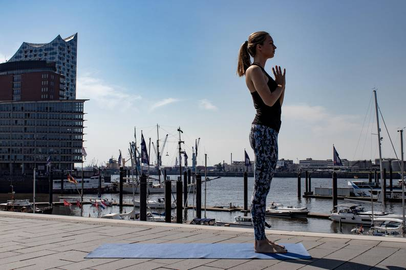 Frau in Sportklamotten beim Yoga.