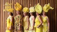 Fünf Frauen posieren in gelben Outfits