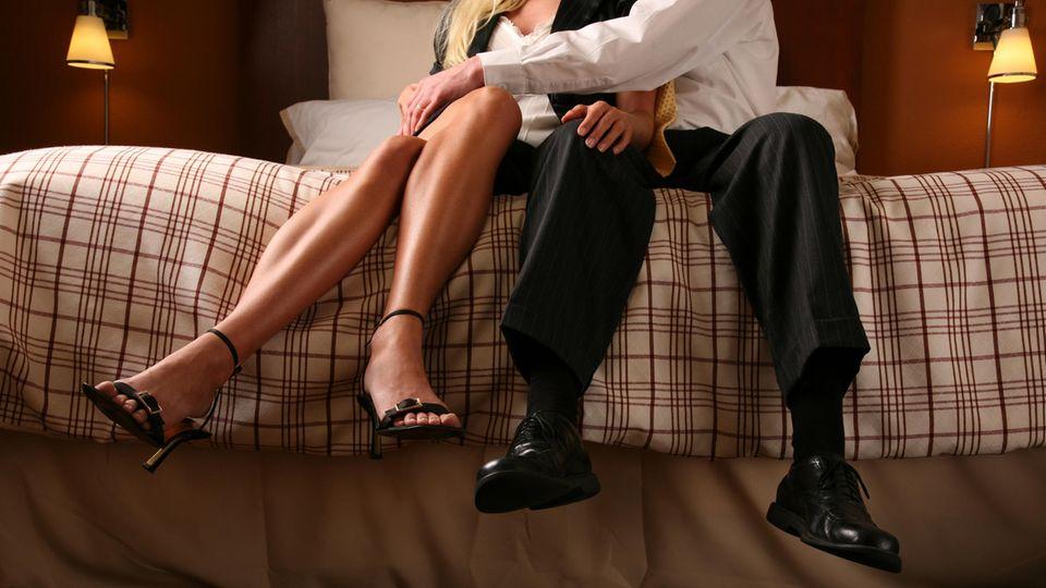 Ein schick gekleidetes Pärchen sitzt auf dem Bett, bereit, eine Affäre zu beginnen