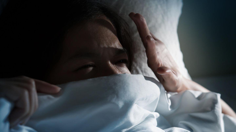 Frau im Bett im dunklen Zimmer