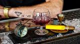 """El cielo rojo  """"Der rote Himmel"""" stieg einst in Guatemala am Haus über den Wolken auf und brachte auf 2300 Höhenmeter würzige Aromen aus den Fässern mit rotem Wein und Schokolade zusammen.Die Weltreise im Ballon beginnt hier! Bei diesem Drink handelt es sich um eine abgewandelte Art eines klassischen Rum-Manhattans, die durch Rotwein-Noten unterstützt wird.      Zutaten:  Ron Zacapa 23  Noilly Prat Red Vermouth  Rotwein-Essenz  Bitters"""