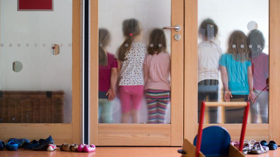Kinder stehen in Kita hinter einer Glasscheibe