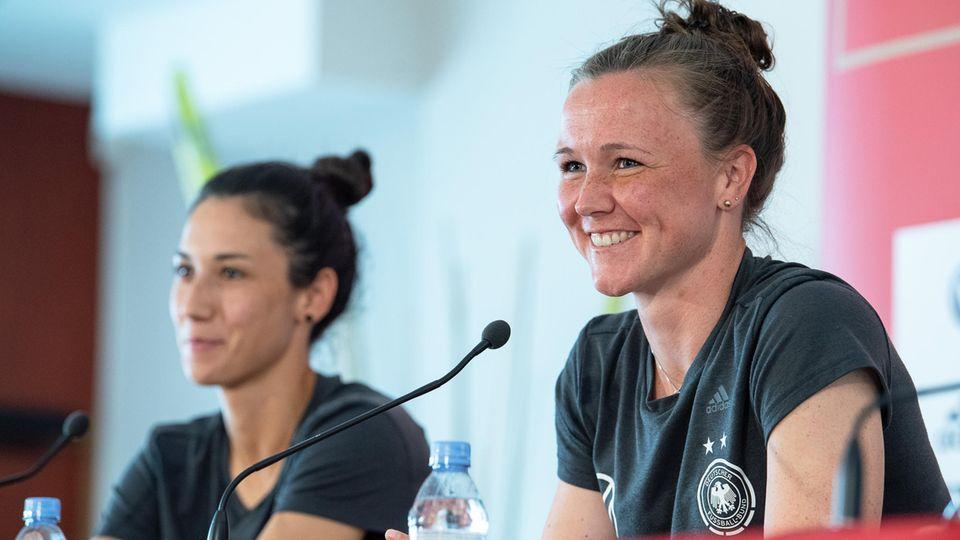 Marina Hegering (r.) spricht neben Teamkollegin Sara Doorsoun bei einer Pressekonferenz des DFB