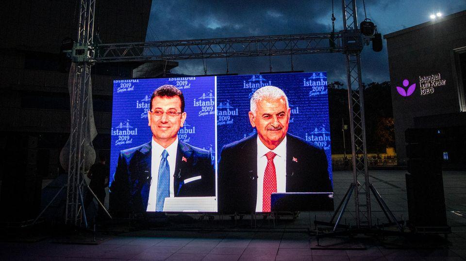 Die beiden Kandidaten Ekrem Imamoglu (l.) und Binali Yildirim sind während einer TV-Debatte auf einer Leinwand zu sehen