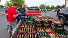Protest gegen Neonazis in Ostritz: Zwei Männer beladen einen Anhänger mit Bierkisten aus einem örtlichen Supermarkt