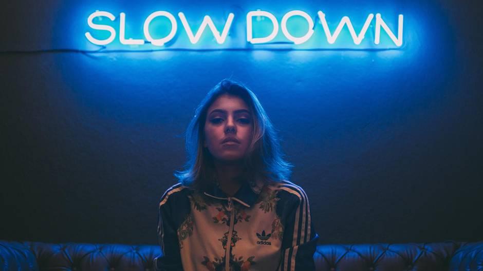"""Neon-Schrift """"Slow Down"""" und Frau mit ernstem Gesicht."""