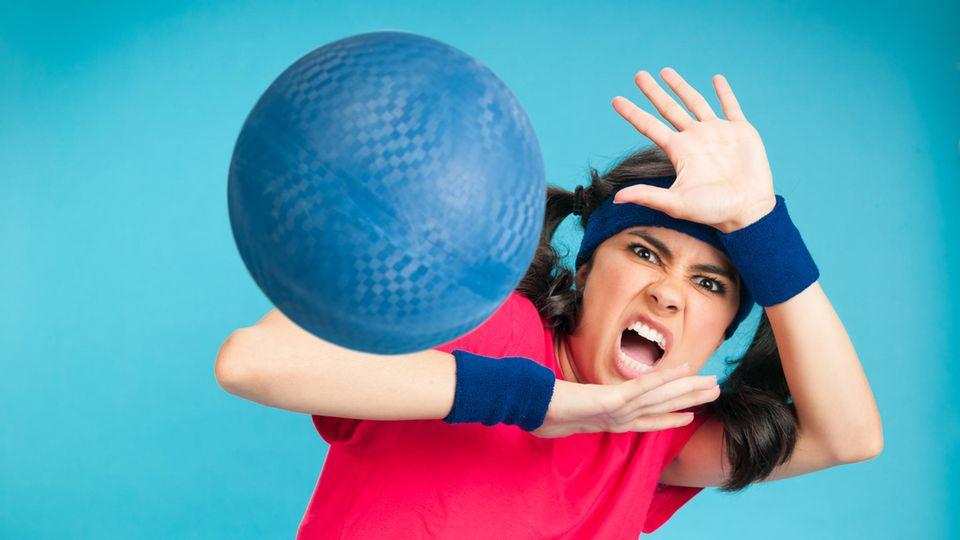 Eine Frau wird beim Völkerball von einem Ball getroffen